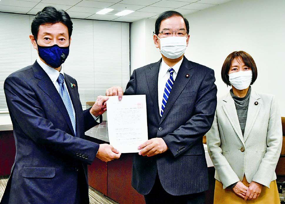 (写真)西村経済再生担当相(左)に要請書を手渡す(右へ)志位委員長と田村政策委員長=12月11日、内閣府