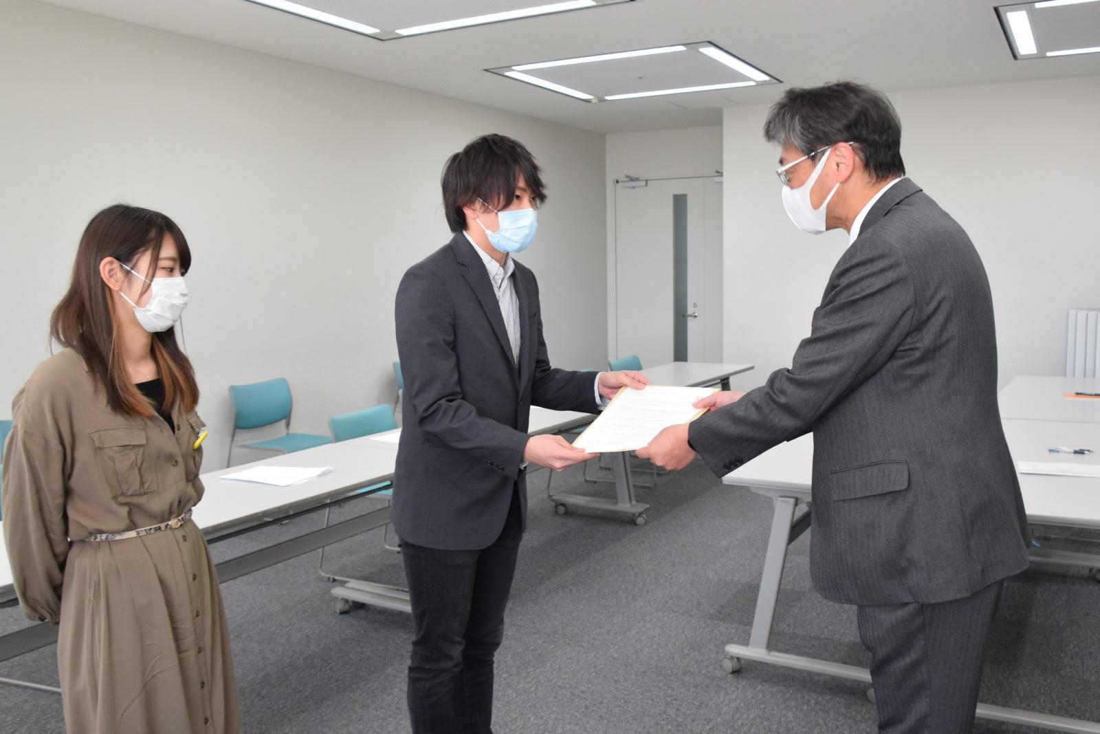 写真:県の担当者(右)へ要望書を手渡す民青石川県委員会の代表